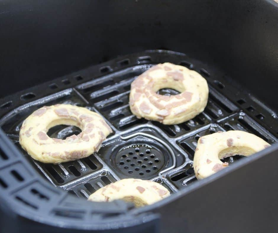 Spray your air fryer basket, with cooking spray. And place your cinnamon roll donuts in the basket.