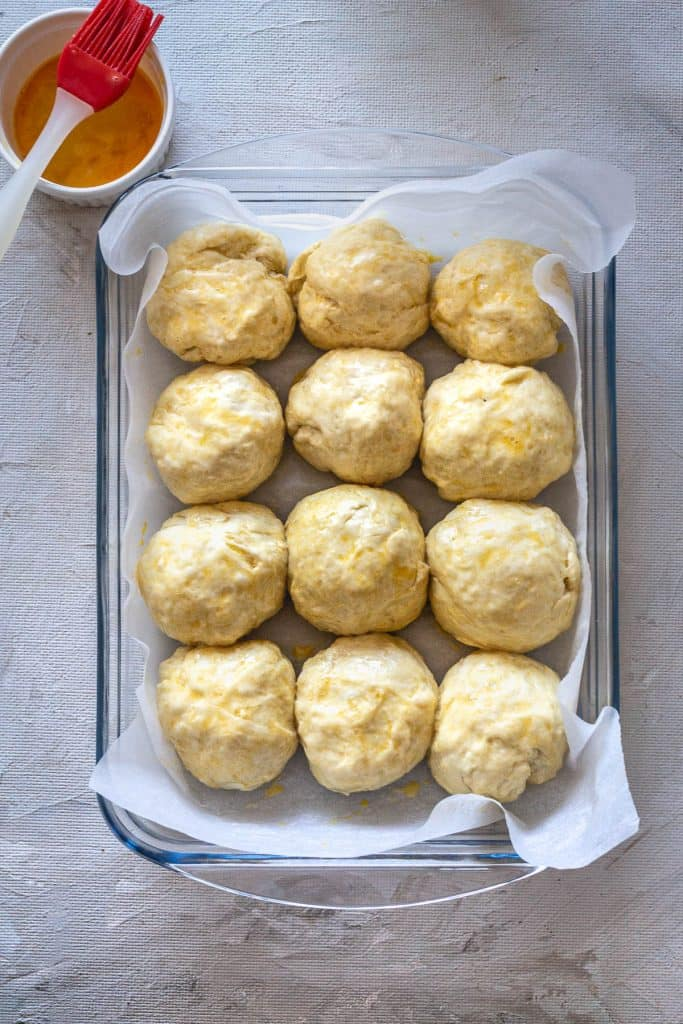 Arrange the rolls into a rectangular pan (7 x 11 inch or similar), lined with parchment paper. Let them sit for 15 minutes in the oven with just the light on.