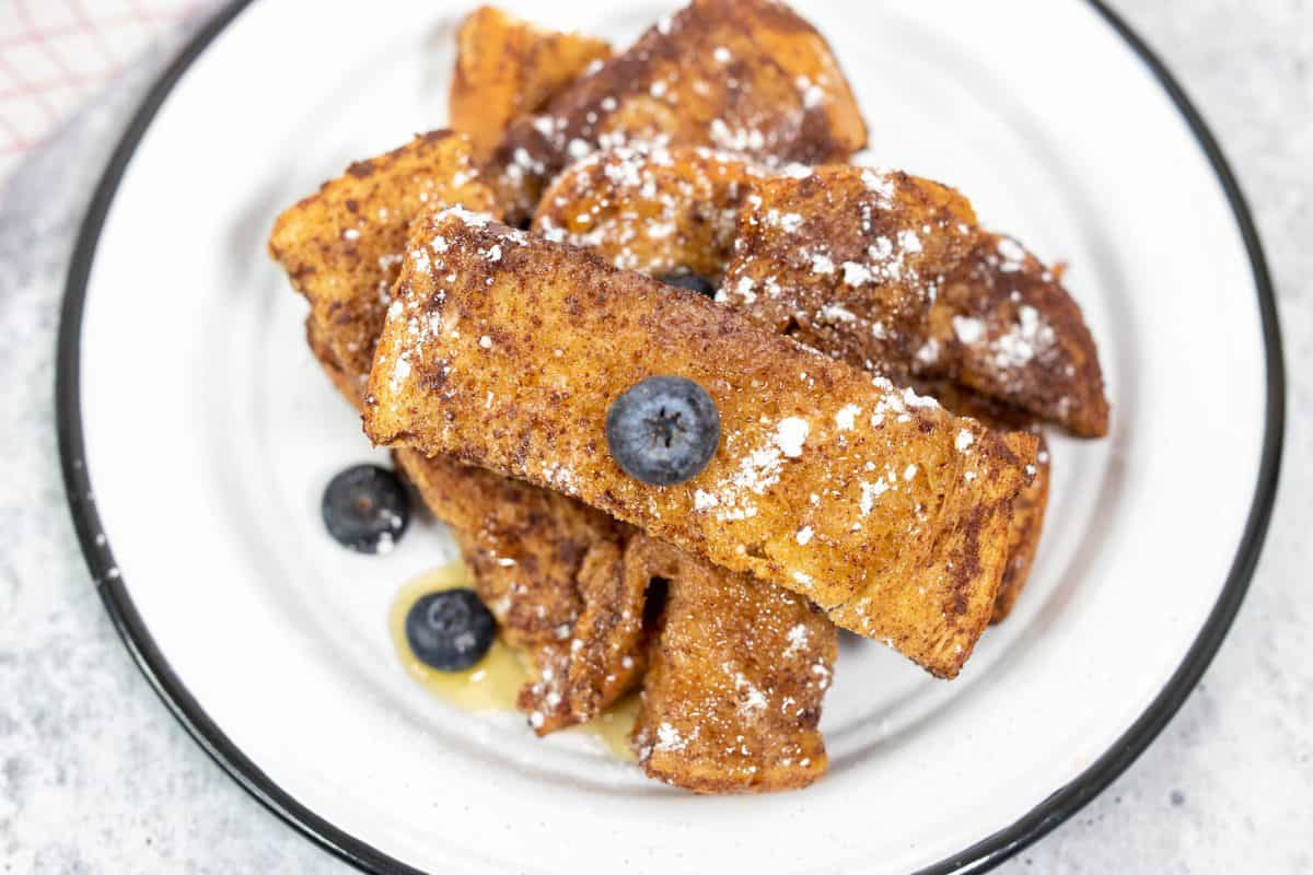 Air Fryer French Toast Sticks on Plate with Powdered Sugar and Fruit on A Plate