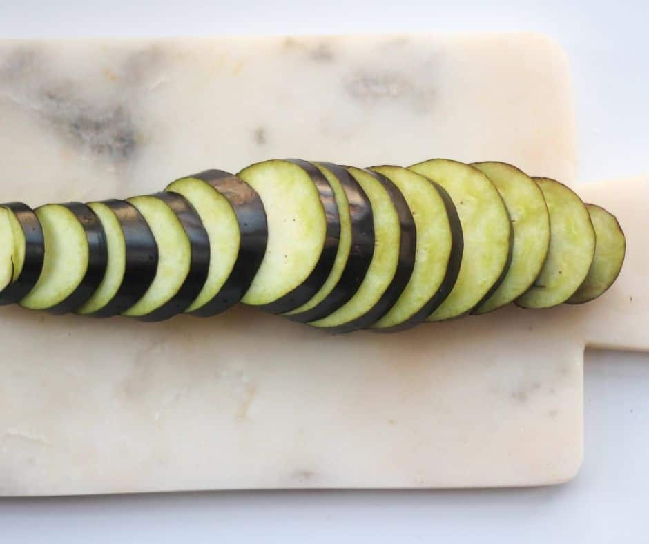 Wash the eggplant, pat dry, then put on a chopping board.  Slice the eggplant into half inch discs.