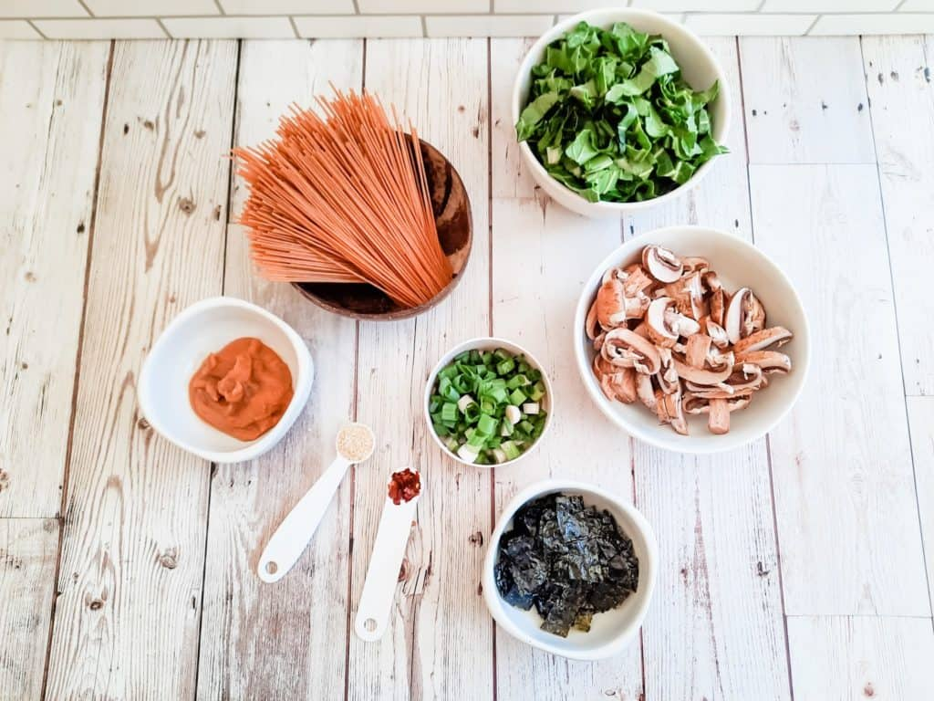 """Begin by preparing the ingredients: chop the seaweed in ¼"""" squares.  Wipe clean and thinly slice the baby Bella mushrooms.  Slice the spring onions.  Thinly chop the Bok Choy greens."""