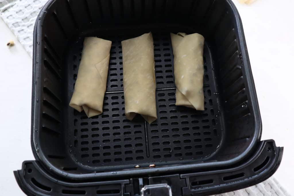 Add the egg roll wrappers to the air fryer basket.