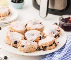 Air Fryer Blueberry Biscuits on a Plate with Air Fryer in Background