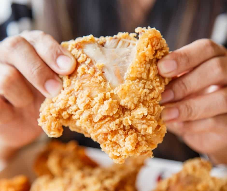 woman holding cooked piece of fried chicken in her hands